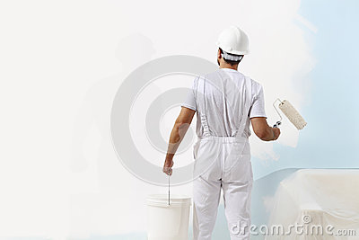 Painter man at work with a paint roller and bucket