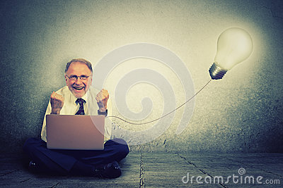 Senior man working on computer with light bulb plugged in it