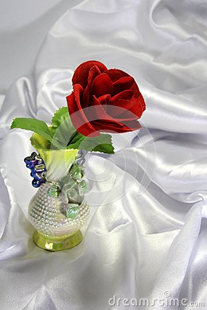 Colored porcelain vase with a red rose