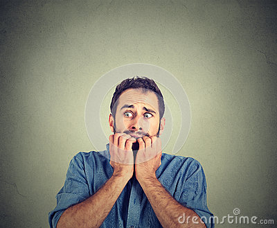 Anxious young man biting his nails fingers freaking out