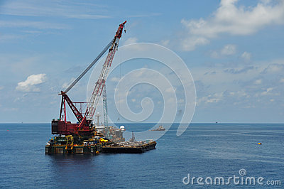 Crane barge lifting heavy cargo or heavy lift in offshore oil and gas industry. Large boat working for lift piping