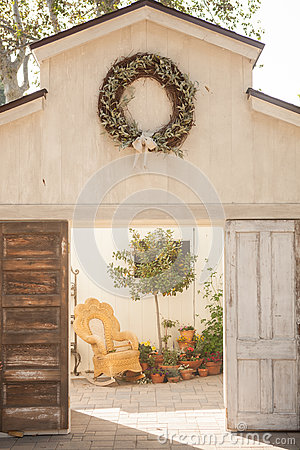 Open barn doors with wreath hanging at the top opening up to a wicker rocking chair