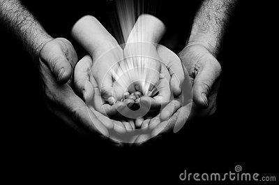 Spark of hope in a child hands wh holding by parents handson dark background. The light of faith