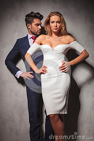 Hot elegant fashion couple standing with hands on hips