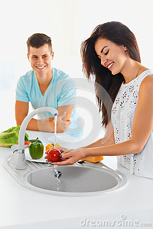 Couple washing vegetables in the kitchen. Focus on the woman.