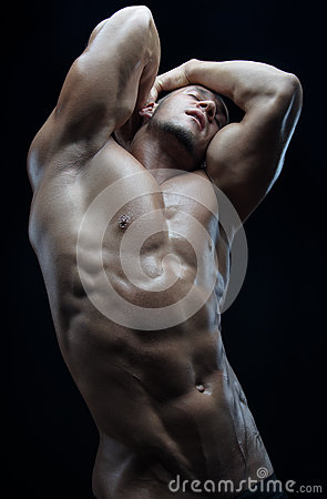 Bodybuilder and strip theme: beautiful with pumped muscles naked man posing in the studio on a dark background