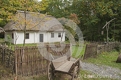 Old wooden house in the woods. Near the house, old horse-drawn background