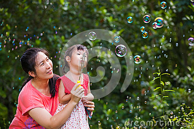 Asian lovely girl and her mother blowing soap bubbles. Family in