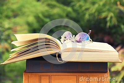 Opened book and glasses lying on stack of books on natural background