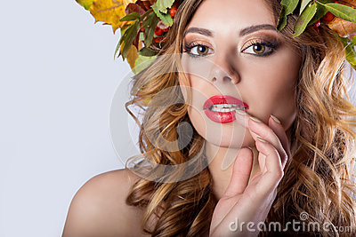 Portraiture style fashion beautiful girl with red hair fall with a wreath of colored leaves and mountain ash color bright tre