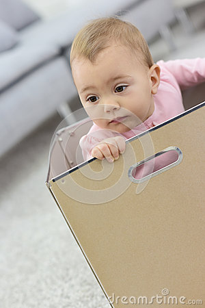 Baby girl playing in carboard box