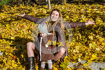 Beautiful young woman girl happy mother playing with her daughter smiling and holding a yellow maple leaves walking in autumn park