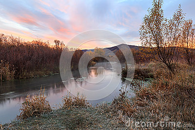 Red dawn morning by a flowing stream in the rural Utah mountains.