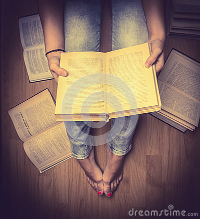 The girl in blue jeans holding a book sitting on the floor,books lying around her ,Student learning study reading close up retro