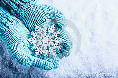 Female hands in light teal knitted mittens with sparkling wonderful snowflake on a white snow background. Winter Christmas concept