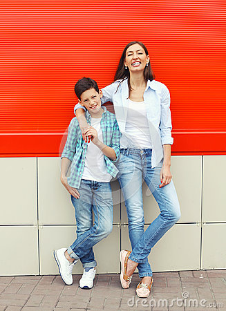 Happy mother and son teenager wearing casual clothes in city