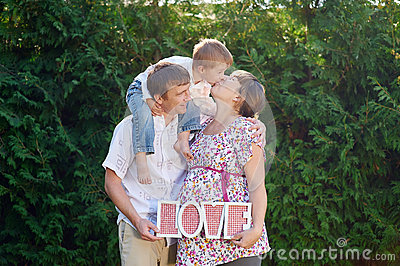 Family of mother father and boy, little boy kissing his mom and parents takes letters LOVE