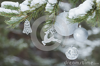 Part of decorated Christmas tree with animal Santa Claus's reindeer ornament and silver baubles on snowy branches