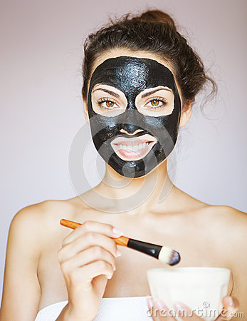 Young woman applying a mask for the face of the therapeutic blac