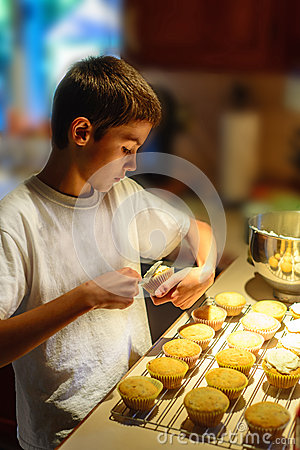 Boy Putting Icing on Cupcakes.