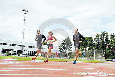 Group of young people running on the track field