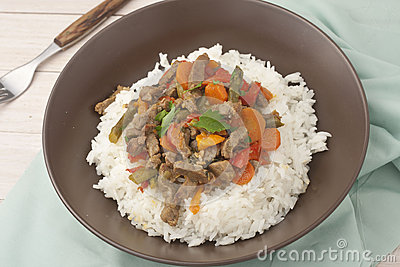 A brown bowl of white rice with stir fry beef with