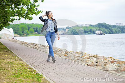 Young beautiful girl in blue jeans and a black leather jacket on