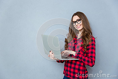 Portrait of young smiling woman standing and holding laptop