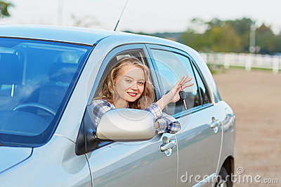 Woman looking out of the car window and holding a key