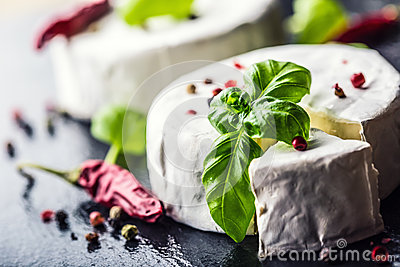 Brie cheese. Camembert cheese. Fresh Brie cheese and a slice on a granite board with basil leaves four colors peper and chili pepe