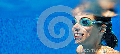 Child swims in pool underwater, girl in goggles has fun