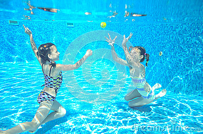 Children swim in pool underwater, girls have fun in water,