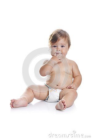 Adorable baby boy sitting with fingers in his mouth