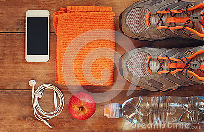Fitness concept with sport footwear over wooden background. top view image