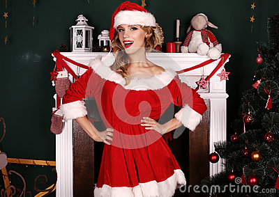 Blond girl wears Santa costume,posing beside Christmas tree and chimney