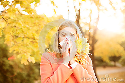 Girl with cold rhinitis on autumn background. Fall flu season. I