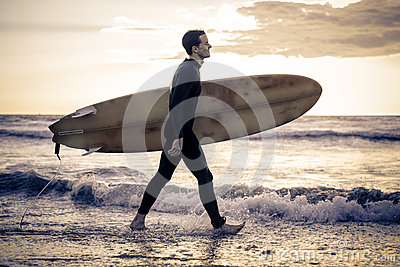 Surfer wals on the beach