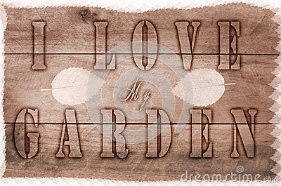 Word I love my garden written, burned letters on wooden brown background