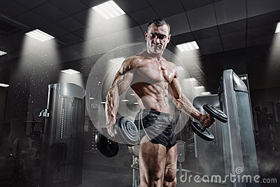 Handsome power athletic bodybuilder in training pumping up muscles