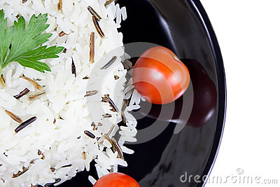 Rice with cherry tomatoes and greens on a black plate