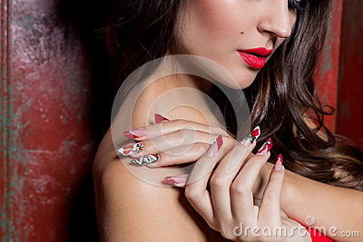 Beautiful well-groomed hands of a young girl with long fake acrylic nails with a festive Christmas pattern on the nails