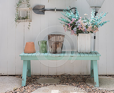 Flower on green bench with white wood panel wall