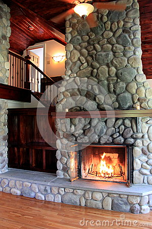 Warm scene in lit stone fireplace showcasing craftsmanship in rustic home