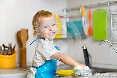 Toddler child washing dishes in kitchen. Little