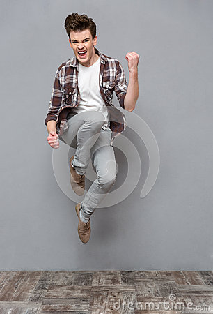 Positive casual young man jumping in the air and smiling