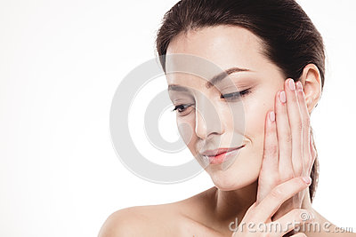 Beautiful woman face close up portrait touching her cheek by palm isolated on white