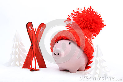 Piggy box with red hat with pompom standing next to red ski and ski sticks on snow and around are snowbound trees