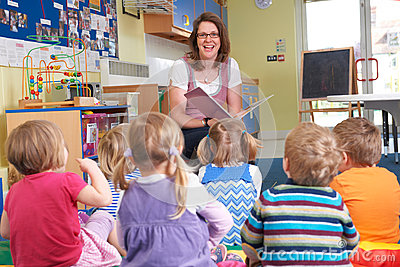 Group Of Pre School Children Listening To Teacher Reading Story