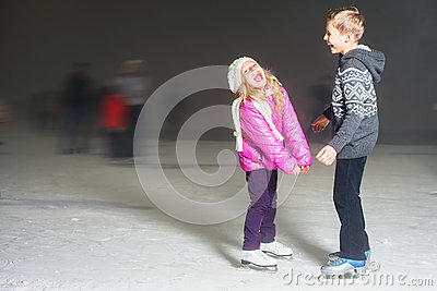 Happy kids laughing at ice rink outdoor, ice skating