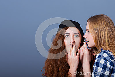Two happy young girlfriends telling secrets. Girl